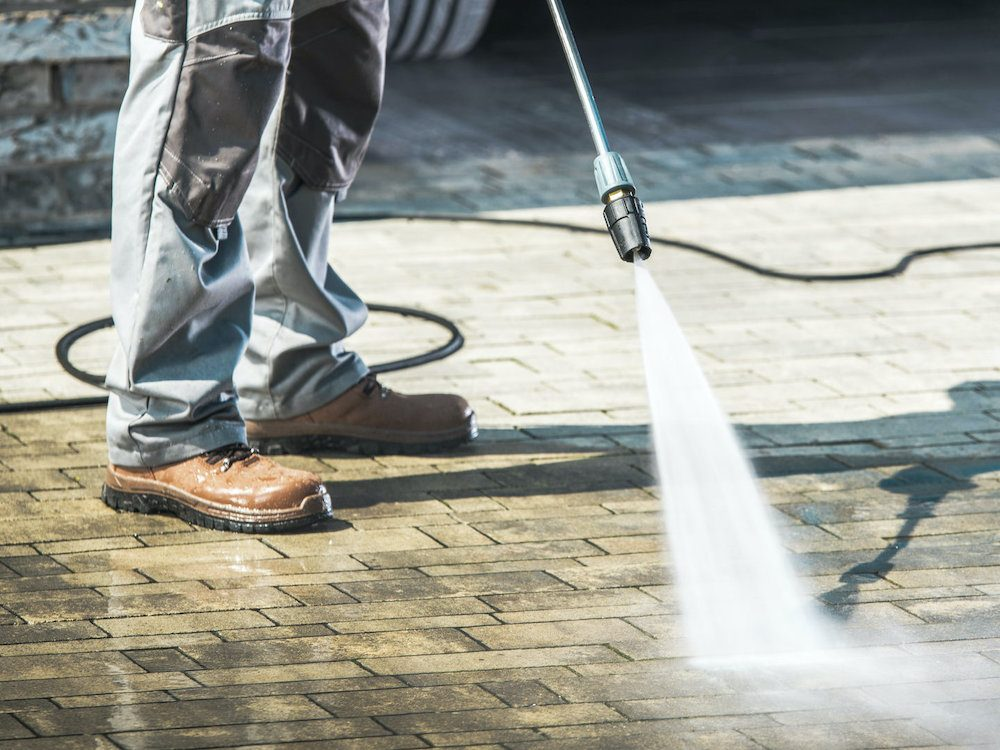 Man using a pressure washer to clean a driveway