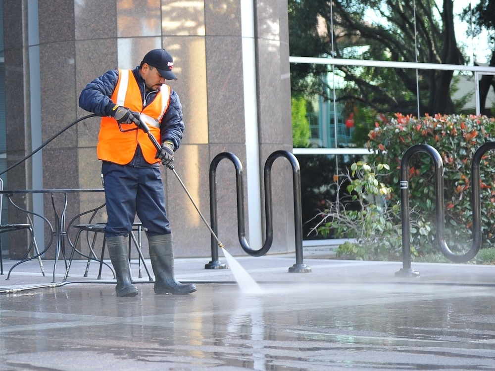 Worker using a commercial pressure washer to clean concrete